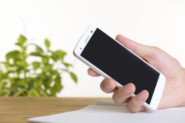 指定口座への振込または「スマホATM」利用なら「19時~20時」までの申込みが目安(スマホを持つ手)