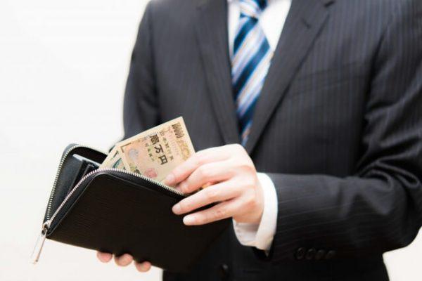 プロミスにおける毎月の返済方法とその金額(財布から1万円を出す男性)